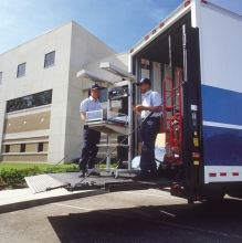 A mendical machine staged for moving off of a lift gate moving van