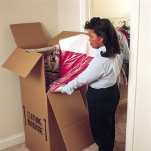 Packing hanging closet clothes into a wardrobe container