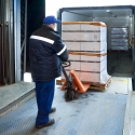 Moving palletized cartons off a truck into storage