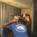 Loading Josephine Meckseper's pump jack art exhibit into 40-foot ocean freight containers for transport to Europe