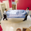 Moving a stretch-wrapped sofa into a customer's residence